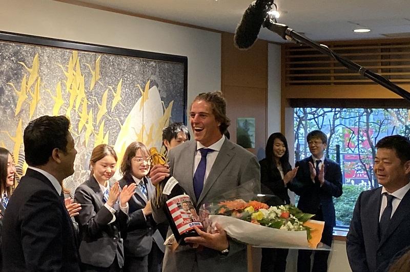 """桜をつけ奮闘した若き""""仕事人""""ジェームス・ムーア、サニックス本社で笑顔のW杯報告。"""