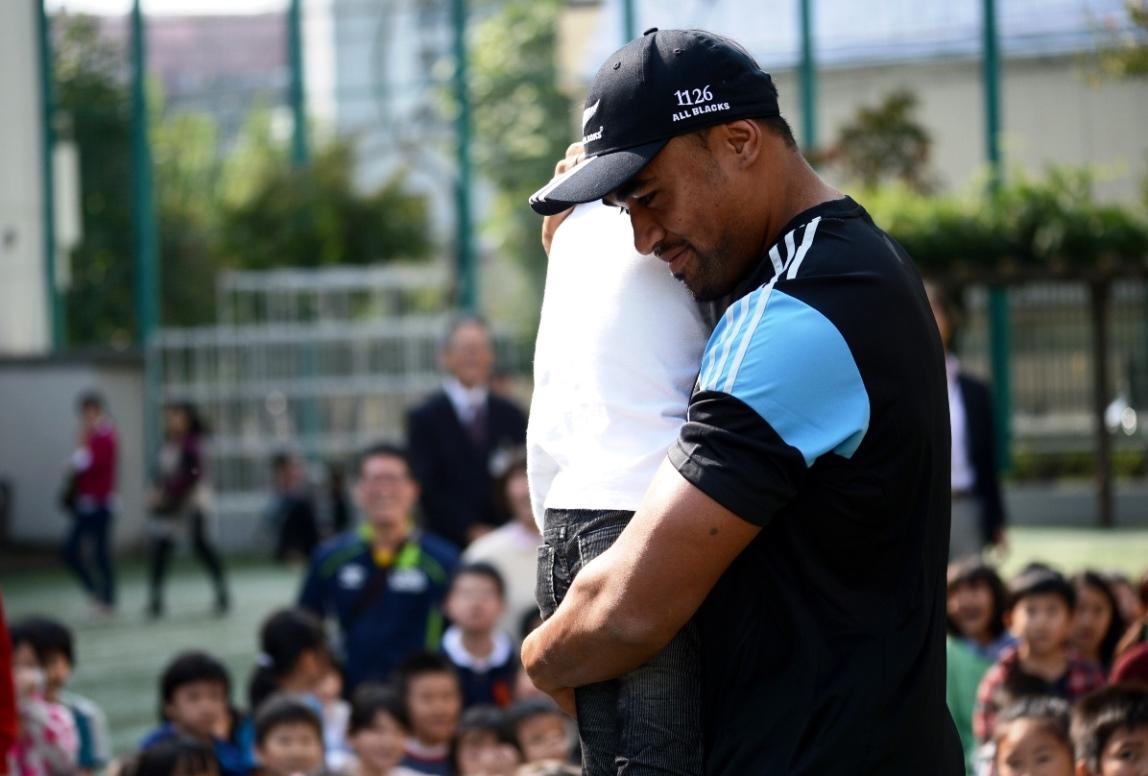 都内小学校でのラグビー教室でボールが顔に当たり泣く少女を慰めるABサイリ(撮影:松本かおり)