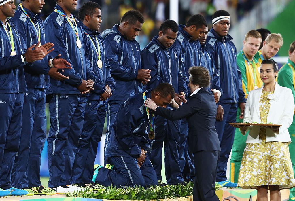 表彰式。フィジーの大男たちは膝を落とし、アン王女から金メダルをもらった(C)Getty Images